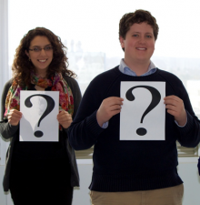 Two co-op students each holding a piece of paper with a large question mark on it