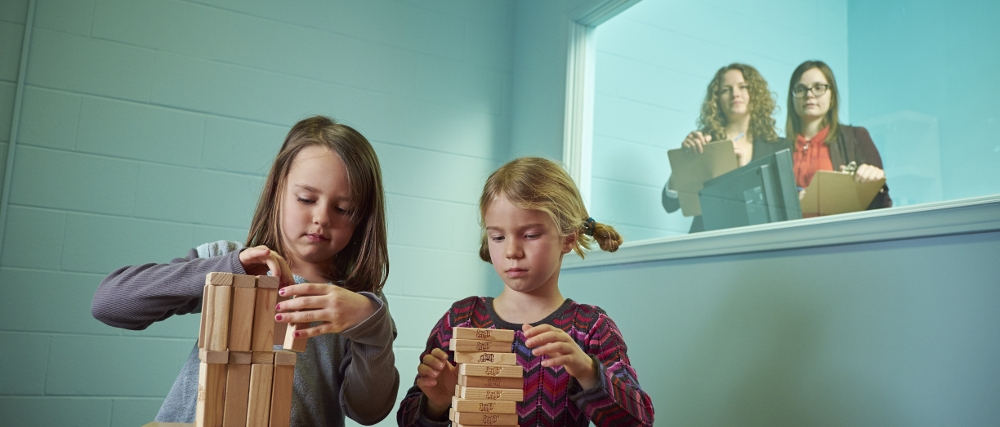 Two girls playing with block as two researcher watch from observation room