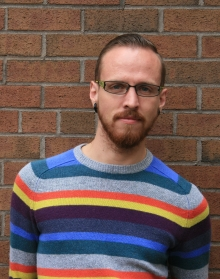 Harrison Oakes wearing a striped sweater and standing in front of a brick wall.