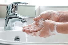 lathered hands rinsing off at tap and sink