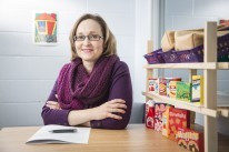 Dr. O'Neill sitting at table with toy shelves beside her