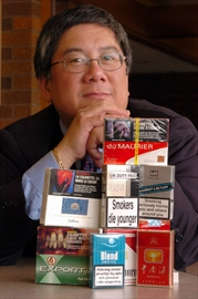 Geoffrey Fong behind stacks of cigarette packages