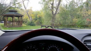 sitting in the car, behind the wheel, looking out at a gazebo in the park