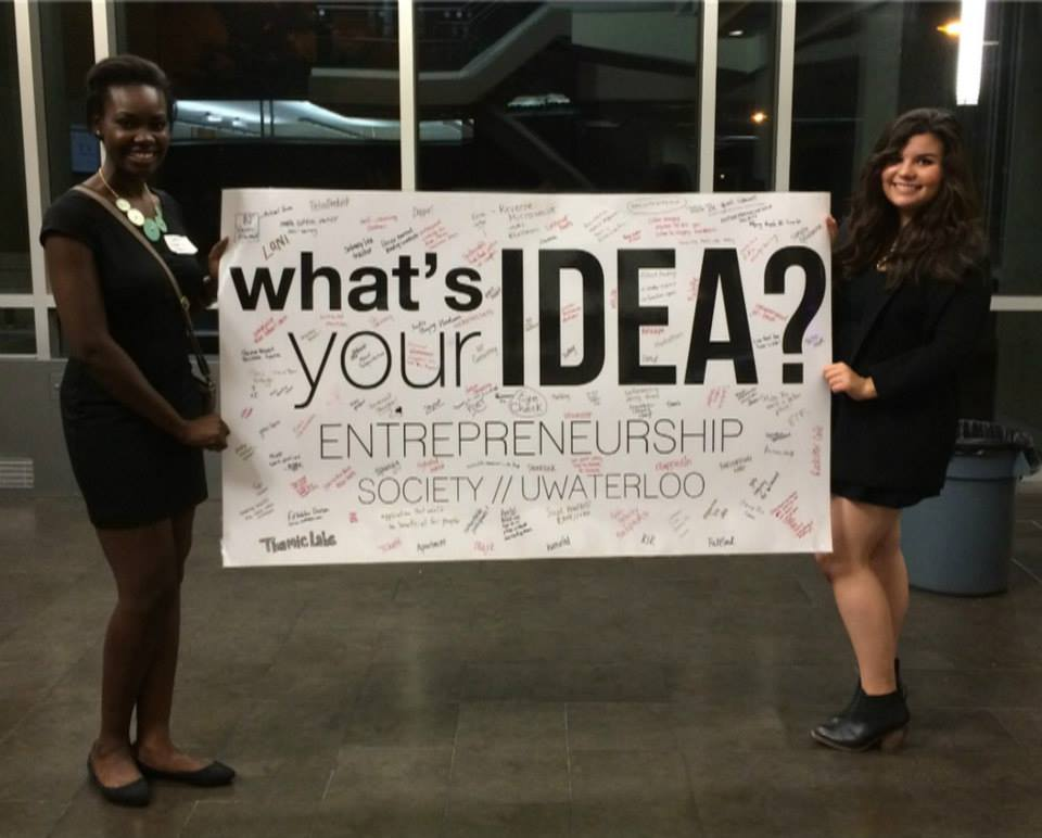 """Two women holding up large """"What's your Idea sign"""""""