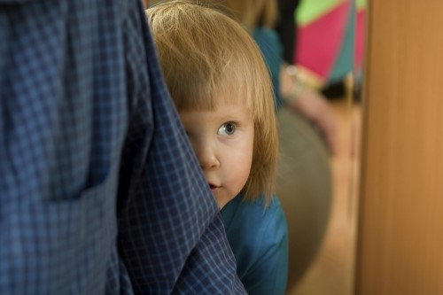 shy toddler hiding behind parent