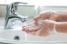 lathered hands rinsing soap off at tap and sink