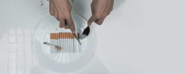 Person cutting cigarettes on a plate