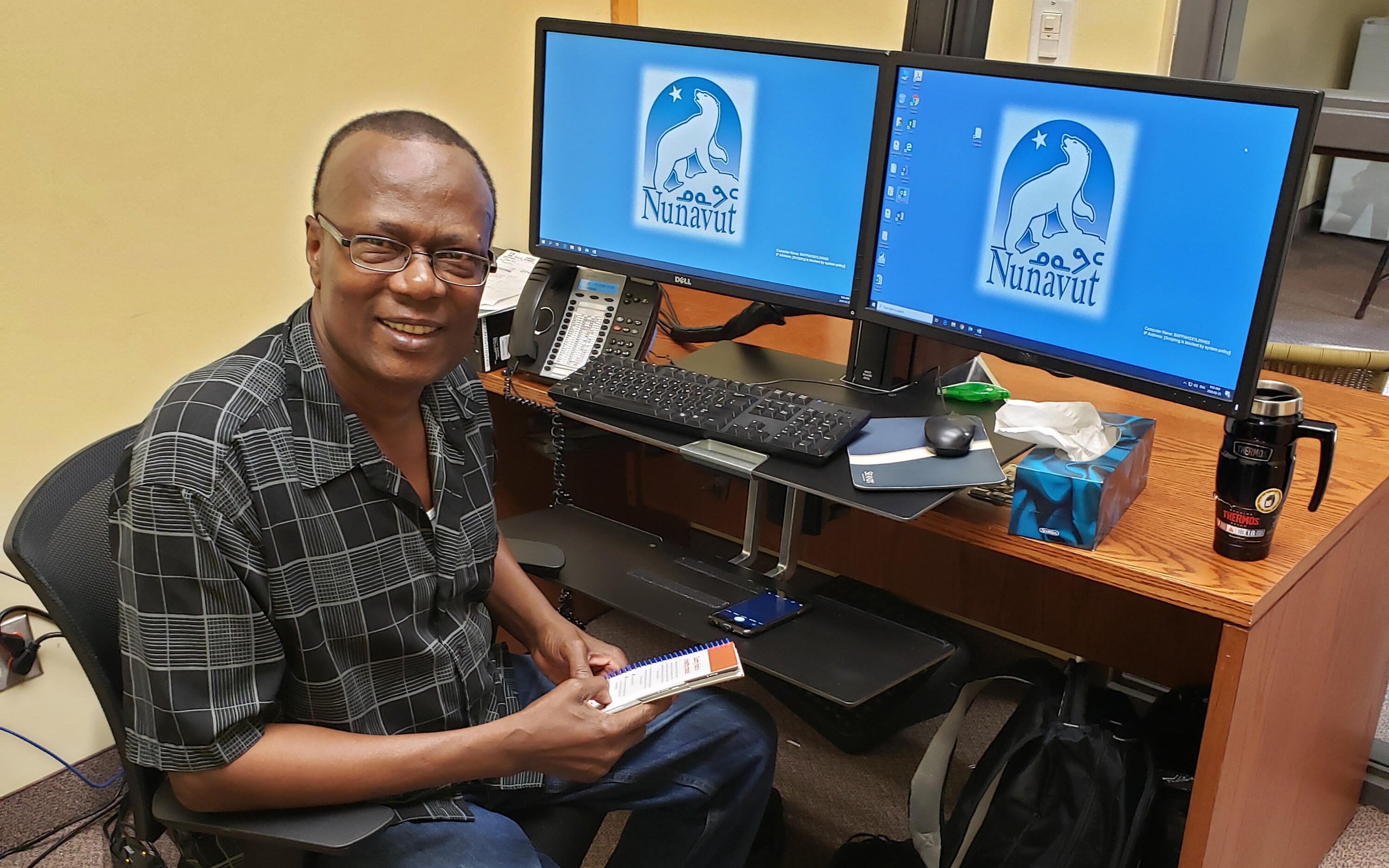 Wilfred Ntiamoah sitting at his computer in his office