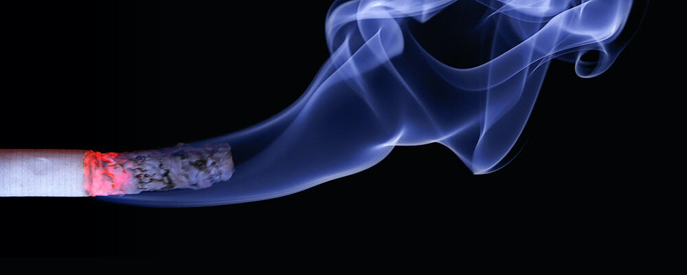 Lit cigarette with flume of smoke.