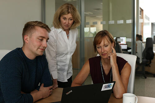 Nicola Mercer with two colleagues discussing something while looking at a computer