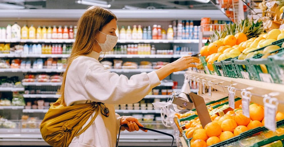 Woman with mask shopping in the produce aisle