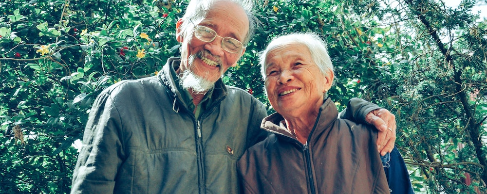 Older couple embracing with greenery in background
