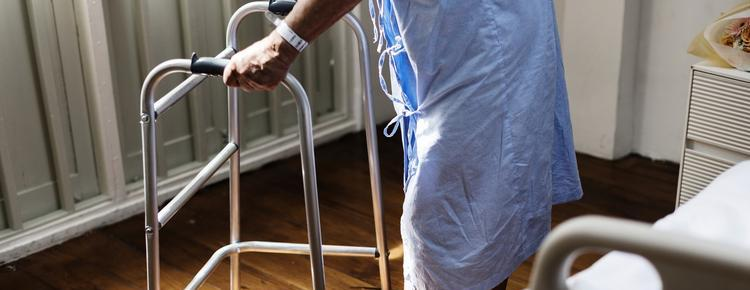 Older adult with a walker in a hospital gown