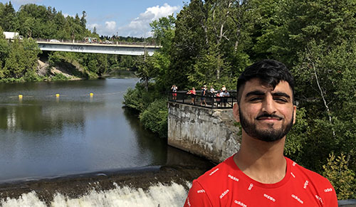 Gurtaj Dhaliwal in front of a bridge over a river