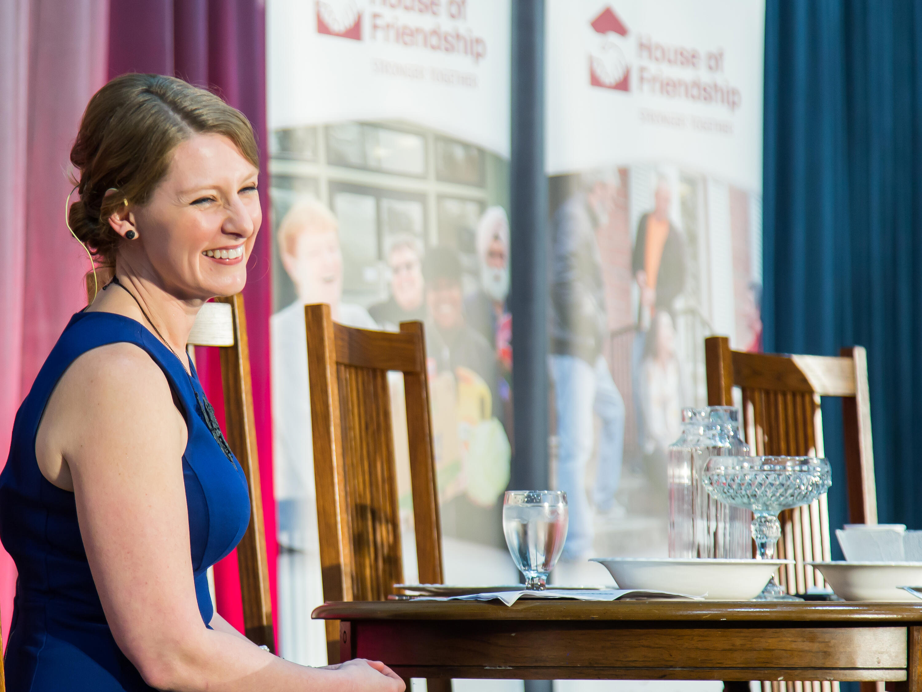 Jessica Bondy smiling while sitting next to a table at an event