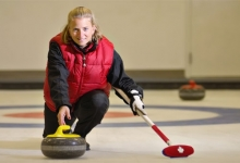 Smiling female curler releases rock down ice.