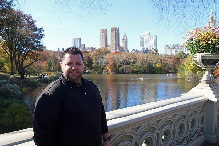 Dylan Flannery standing on bridge over lake in Central Park, New York City