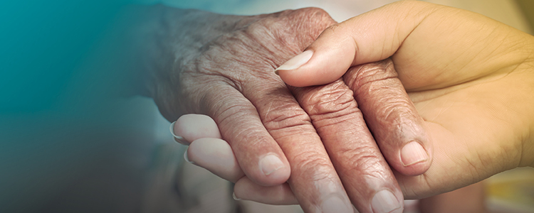 carer hand holding older adult hand