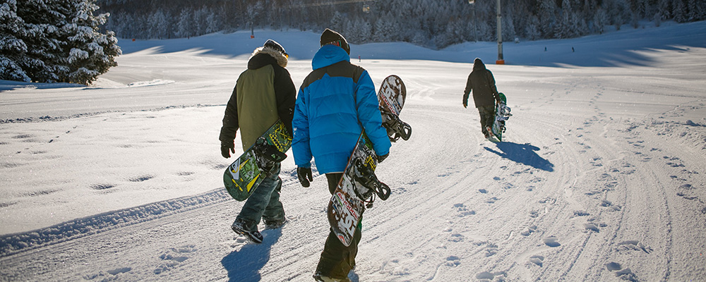 Three snowboarders walking on wintery path.