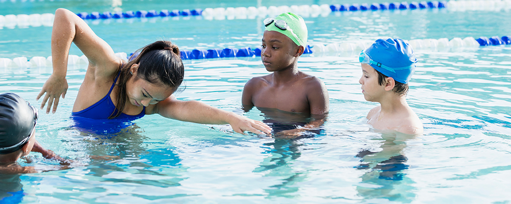 Instructor demonstrating swimming to children.