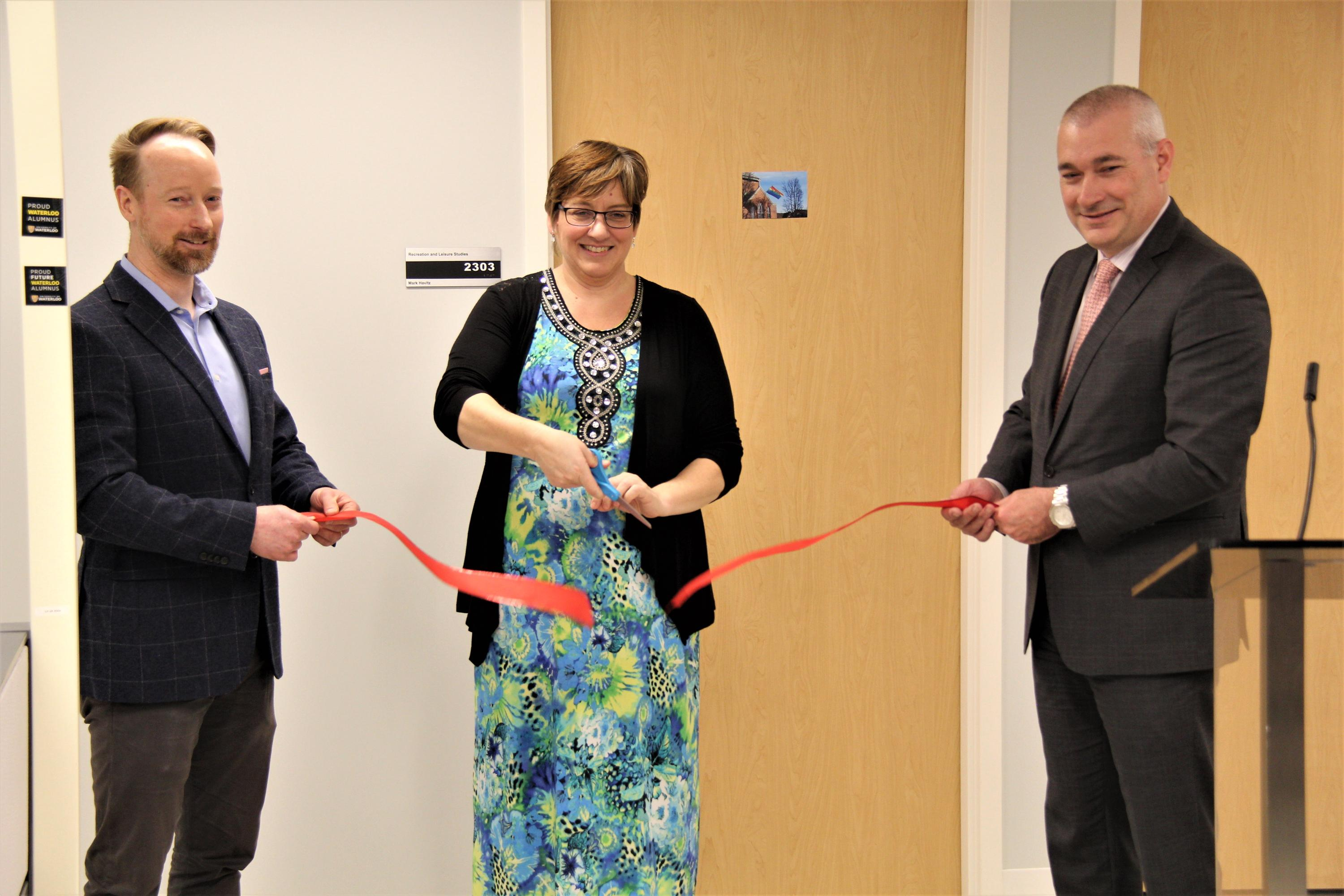 Dr. Troy Glover, Sandy Heise, and Dean James Rush cut the ceremonial ribbon