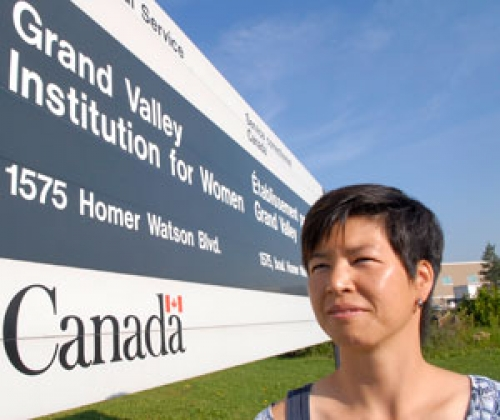 Susan Arai with Grand Valley Institution for Women sign.