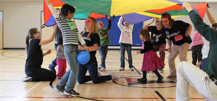 Student volunteers play parachute game with group of kids.