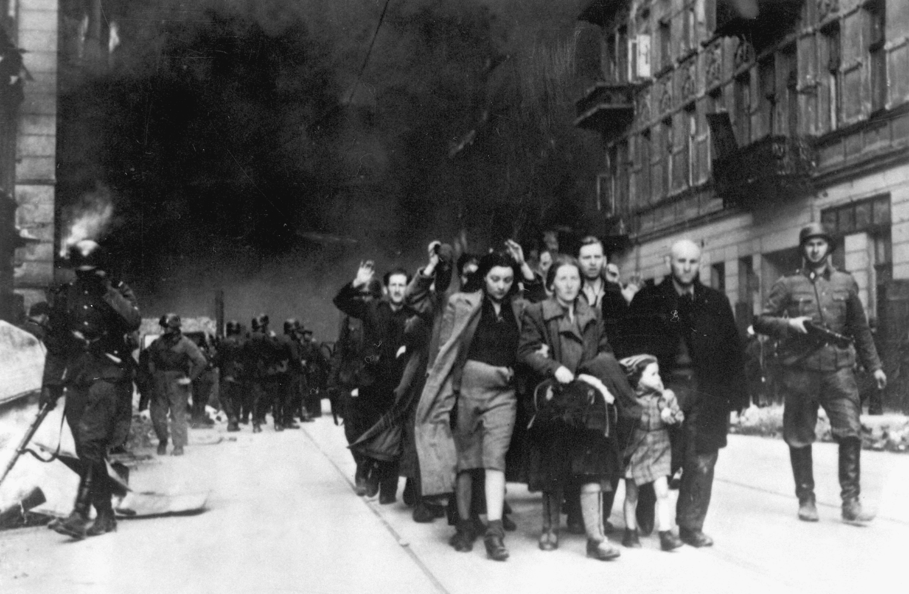 Jews in the Warsaw Ghetto are led to a deportation point sometime between April 19 and May 16, 1943 (Wikimedia Commons).