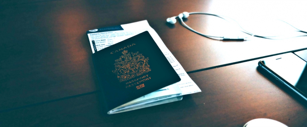 a canadian passport on a desk with headphones