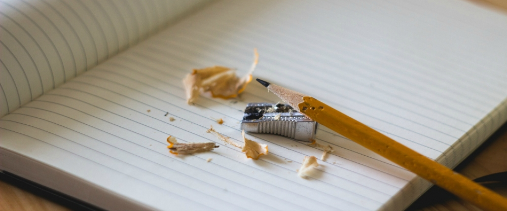 a sharpened pencil and pencil sharpener with pencil shavings resting against a lined notebook