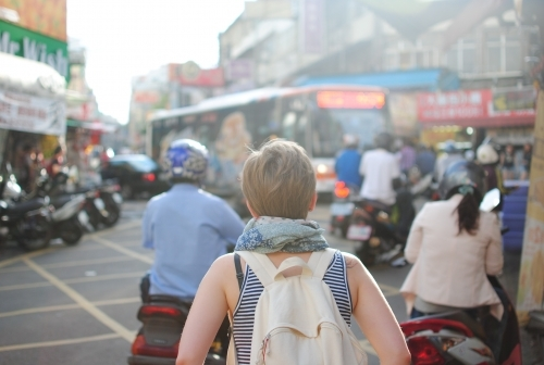 woman with a backpack on her back facing a street filled with people abroad