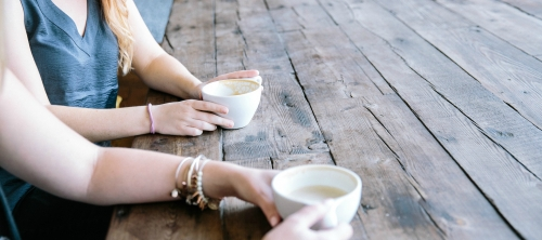 a picnic table with two people sitting and drinking coffee