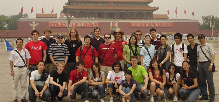 students pose in front of a temple in China