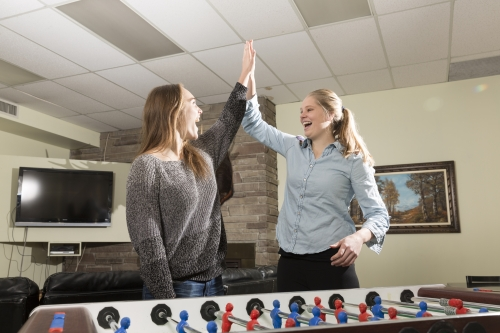 two girls high five over foosball table