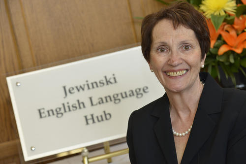 "Judi Jewinski standing in front of a sign that reads ""Jewinski English Language Hub"""