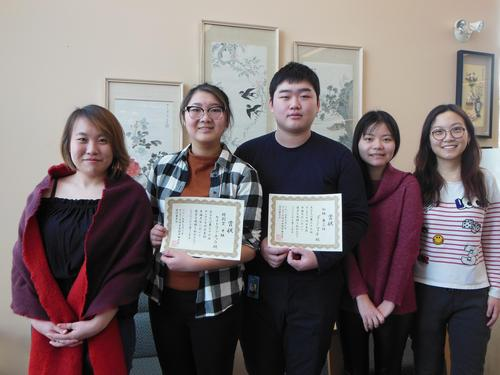 Five students standing in a row, two are holding their winning certificates.