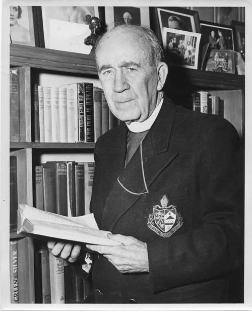 Black and white photo of Bishop Renison in front of a bookcase