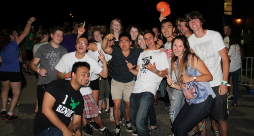 students gather together at an outdoor party for a photo