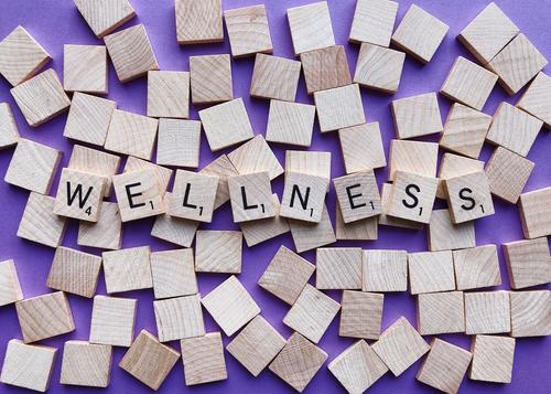 wellness spelled with scrabble tiles on a purple background