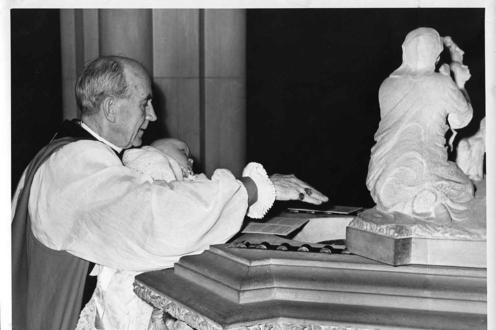 Photo of Bishop Renison baptizing his grandson, 1950
