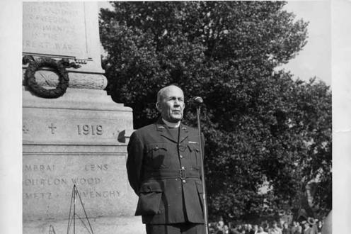 Photograph of Rev. Robert J. Renison in front of the North Bay cenotaph