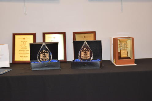3 award plaques behind 2 glass awards with the UAE logo, and a box with a golden award, also with the UAE logo