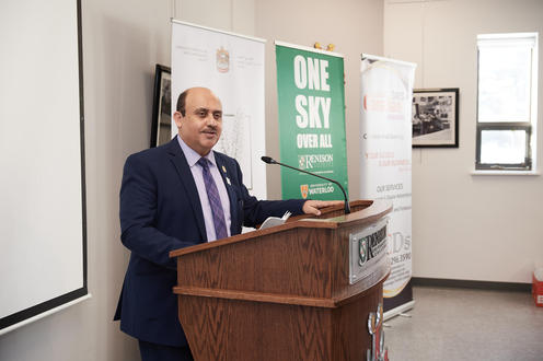 Dr. Ahmed Bourini standing at a podium with the Renison logo.