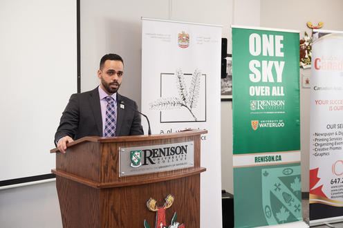 The United Arab Emirates representative speaks at a wooden podium with the Renison logo on the front.