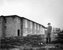 The Ven. Harvey Southcott standing next to Renison College under construction (1962)