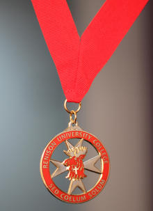 The badge of Renison (a red moose head on a Maltese cross), encircled by a red ring, hanging from a red ribbon