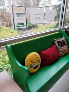 "Green bench with an emoji cushion, a red cushion, and a patterned cushion. Above the bench, on the window behind, is a poster with the title, ""connection bench."""