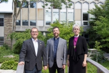 The Rt. Rev. Linda Nicholls (r) standing on the Renison garden walking bridge with Brendon Bedford (l) and Rev. Greg Jenkins (c)