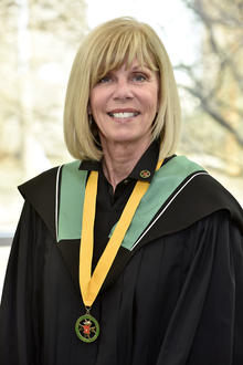 Janet Menard wearing a BA hood and the medal of a Distinguished Alumna of Renison University College.
