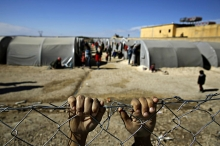 child puts hands on top of chain link fence with refugee camp in the background